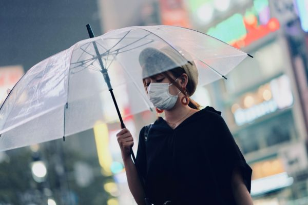 A woman walks in Japan wearing a surgical mask.